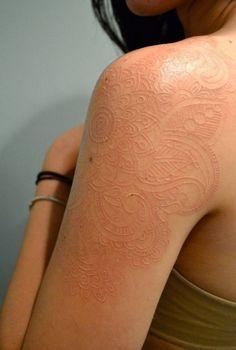 Elegant white ink tattoo on shoulder