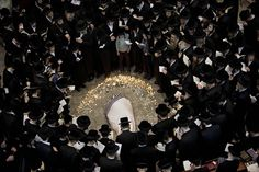 LEADER LOST: Ultra Orthodox Jewish people gathered around the body of Rabbi Moshe Yehoshua Hager, leader of the Hasidic sect Vizhnitz, at a synagogue during his funeral procession in Bnei Brak, Israel, Wednesday. The rabbi was 95 years old. (Oded Balilty/Associated Press)
