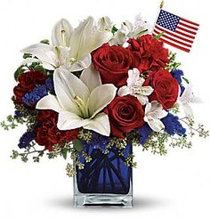 Lush red, white and blue flowers are presented in a deep blue glass cube vase along with an American flag.