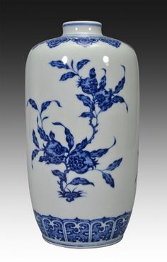 A BLUE AND WHITE VASE, Qing Dynasty. The vase is wide pear-shaped. The exterior is decorated with pre-blossomed flowers connected by vines, leaves, and twigs. The vase's top and bottom layer are decorated with imperial designs. The bottom is decorated with Chinese characters. 10 in. tall.