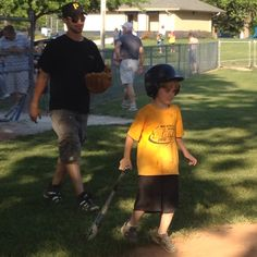 Proud father/coach taking his son to hit the baseball for the first time at his first ever game.