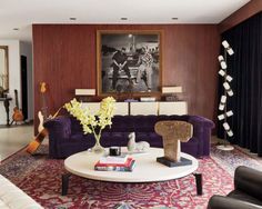 Home to Adam Levine, the lead singer of Maroon 5, this space has a vintage aesthetic. Coincidentally, his space is lined with mahogany paneled walls that offer a maroon-like appeal. Ivory colored lamps, chests, and flooring add to the mid  century undertone of the space while a plum Chesterfield sofa adds a wild pop of royal color. Subtle global ornamentations, and an urban black and white photograph round out the eclectic energy which displays Adam Levine's hard to pin down nature.