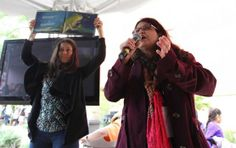 Author Carolyn Dee Flores (right) reads aloud a story from one of her books as volunteer Akiko White holds up the book for the audience to s...