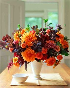 A china vase holds 'Ben Huston,' 'Old Gold,' 'Anries' Orange,' 'Prince Noir,' and 'Jomanda' dahlias creating a beautiful and lush fall arrangement.