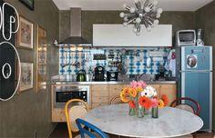 Psicodélica, a cozinha tem um painel de 80 azulejos de demolição de 1973 (Museu dos Azulejos). Cimento queimado reveste as paredes da área, que também abarca a sala de jantar. Cadeiras Thonet da Isto É Brasil e pendente da Benedixt. Projeto de Rodrigo Angulo.