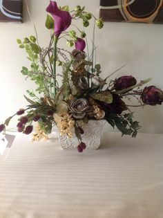 This gorgeous calla lily arrangement consisting of two beautiful calla lilies, artichokes, roses, and draping ornamentation. An exquisite, inspirational design with radiant color combinations. Would be beautiful on a side table or an entryway table