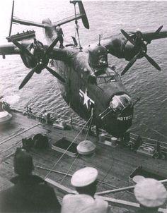 A U.S. Navy Martin PBM Mariner of Fleet Air Wing 6 is hoisted aboard the seaplane tender USS Curtiss (AV-4) after a mine-hunting patrol off North Korea during the Korean War (1950-1953).