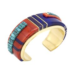 Charles' used the very best material of gem quality Lone Mountain turquoise, Mediterranean coral, lapis and sugilite to creat this 18k gold kachina bracelet.  Measures 5 3/4″ with a 1 1/4″ opening.  1 1/4″ width.