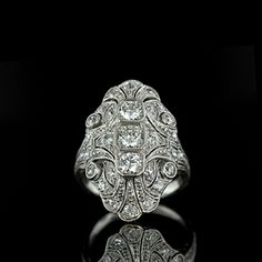 Absolutely fabulous Edwardian platinum diamond dinner ring featuring three European cut diamonds carat total weight, H-I color, clarity) set down the middle in octagonal milgrain settings and accented by twenty six European cut diamonds