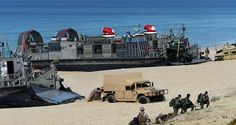 US marines push a Humvee stuck on the sand as they disembark from the overcrafts deployed by the USS Arlington amphibious transport dock during the NATO's Trident Juncture exercise at Pinheiro da Cruz beach, south of Lisbon, near Grandola on October 20, 2015
