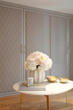 Elegant gray fabric closet doors embellished with brass and lucite vertical pull handles boast a geometric, triangular pattern that adds dimension and class.
