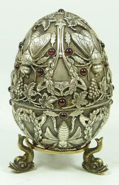 Russian silver egg. Has intricate raised design depicting flies, wreaths and grape clusters. Mounted with Cabochon garnets throughout. Gold wash interior.