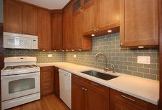 Kitchen backsplash with oak cabinets and white appliances