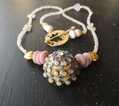 Lori Lochner lampwork urchin with rose quartz and gold vermeil.