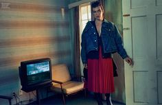Milla Jovovich layers up in Balenciaga denim jacket, sweater, pleated skirt and boots