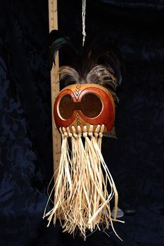 Looks like an owl.  Used stains, rooster feather, raffia and woodburned design.  #hawaiian