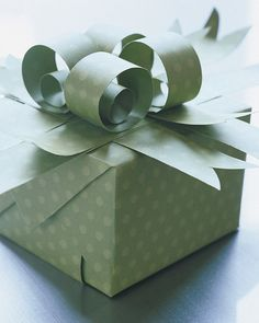 Use wrapping paper to create four beautiful curlicues atop your gift box.
