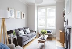 Soft grey tones and crisp white details bounce light around this contemporary living room. Pale wooden furniture also helps to keep the room looking bright and airy.