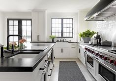 Step into this beautiful black and white contemporary kitchen boasting white shaker cabinets finished with oil rubbed bronze pulls continuing onto a large kitchen island boasting a white undermount prep sink with a black deck mount faucet and a built in microwave.