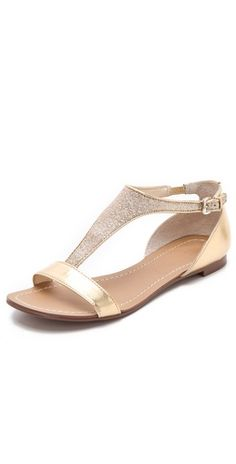 Boutique 9 Piraya Glitter Sandals. Covered in metallic glitter, the T-strap of these imitation-leather sandals lends a luxe, playful feel to a classic Boutique 9 silhouette.