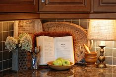 baskets and lamp on kitchen counter. LOVE the old grater as a flower vase. rustic. Love the open book too!