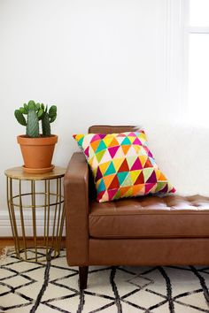 Love this geometric pillow, cacti and rug!  Would be very easy to do a DIY rug like that... Hmmm......