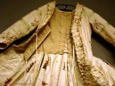 Robe à la française from the inside, c. 1760 The robe has a wide strip of white linen down the front stiffening the edge and holding pleats and robings in place. The top is mounted on a linen bodice with a centre back lacing to adjust the width, and centre front lacing to close. The stomacher is inserted into the gap between the fashion fabric and lining hiding the lacing.