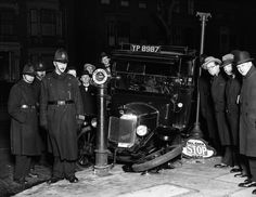 "A group of policemen and passers-by survey the wreckage of a taxi in Stoke Newington, London. Its front wheel lies on the pavement next to a sign bearing the ironic instruction ""All Cars Stop Here"". 14th February 1930."