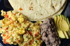 This version of migas has eggs, peppers, cheese and fried corn tortillas. Cook them together and then serve with refried beans, avocado, and flour tortillas.