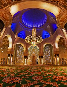 Abu Dhabi's Grand Mosque, from the inside. A panorama of the inside of the amazingly ornate and decorated Sheikh Zayed Mosque in Abu Dhabi, UAE. At 500 million USD, this is the world's largest chandelier and world's largest rug.  The 99 Names of Allah inscribed in the wall and lit up, the seven chandeliers hanging above and the array of lights take up 40% of Abu Dhabi's electrical grid!