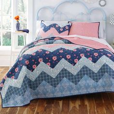 The Camilla Reversible Quilt Set includes a quilt and sham(s). Bedding combines zigzags, florals, geometrics, and lines to create a fun and lively display. This cotton ensemble includes the colors of navy, light blue, sky blue, white, and coral. Quilt has printed patterns, quilting, and bound edges and is reversible to a geometric pattern in coral and white. Reversible sham(s) mimic the quilt and back and have a zipper closure.