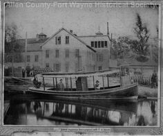 "The ""Amelia,"" a steamboat owned and operated by the Centlivre brothers, founders of the Centlivre Brewing Company, Fort Wayne, Indiana. Picture was taken on the feeder canal looking east towards the Brewery in the early 1880's. Persons on the boat, left to right are: Charles L. Centlivre, founder of the brewery, Engineer (unknown), Peter Nussbaum, Brewmaster, Louis Centlivre. 1880-1889."