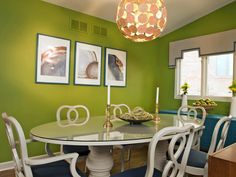 The vibrant color palette and modern light fixture give this room a fun aesthetic while the glass-top table and large credenza make the space functional for family gatherings.
