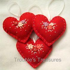 Felt heart - attach buttons, embroider lazy daisies and French knots. Stitch, fill with batting, close.