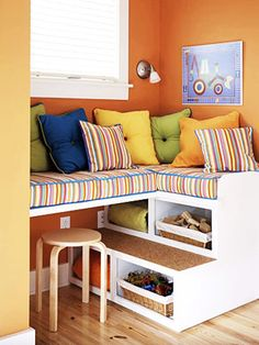 kids bedroom small space idea storage under window seat love the colors too! from BHG