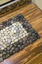Some river rocks and glue is all that is needed to transform an inexpensive plain doormat into high-end catalog replica as shown on Oregon Live.