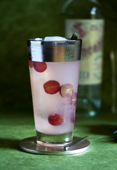 harvest smash | 10 red grapes, halved, plus more for garnish  2 ounces Pisco, such as Encanto de Campo  1 ounce St. Germain  1/2 ounce freshly squeezed lime juice  Ice  Chilled club soda  1 sage leaf