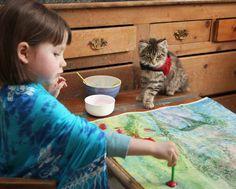 Ensaio fotográfico revela a amizade comovente de uma garotinha autista de cinco anos, que pinta lindas telas com seu gato terapêutico.