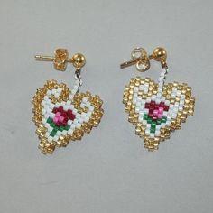 Ces magnifiquement les boucles doreilles fabriqués à la main sont faites avec tissage de perle complexe pour former un coeur avec une petite fleur au centre. Les bords sont faits dans une perle dor doublée argentée et donnent une sorte de modèle scroll. Les postes de loreille