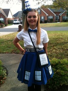 Dr Who TARDIS costume. Made with a blue circle skirt, the windows are white felt with black  ribbon, and just tacked on for easy removal. I found the cool fabric at Spoon flower for the belt and the purse. My awesome sister made the headband out of a painted clear cup.  You can't tell from the photo but I had little LED battery lights that I put in the cup.