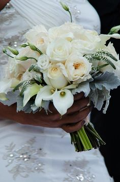 A white and cream bouquet of roses and hydrangeas is accented with light and dark green touches.