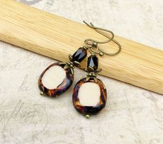 This is a lovely handcrafted pair of brown and cream earrings. It combines Czech glass beads with antique gold accents to create a very unique and beautiful piece of jewelry. This earring can be worn dressed up for a night out on the town, yet would be perfect for a casual day of