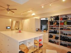 The dresser island in RMS user flgirlaol's closet stores plenty of items, including hats, workout equipment and books. The all-white cabinetry makes the large space feel more open, and track lighting brighte… more