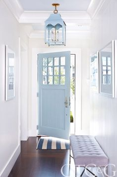 A coastal blue door invites guests into a clean, classic foyer.