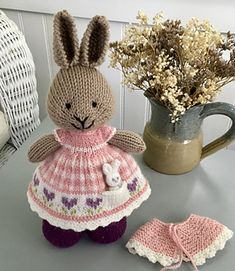 This little bunny is wearing a sweet gingham dress with heart flowers along the hem. The dress also features a pocket which holds her very tiny toy bunny. She's keeping off the early spring chill . Knitted Bunnies, Knitted Animals, Knitted Dolls, Crocheted Toys, Knitted Baby, Crochet Bear Patterns, Knitting Patterns, Crochet Cats, Crochet Birds