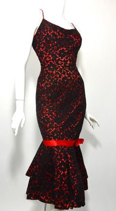Bombshell black lace and red taffeta late 50s cocktail dress. Fitted to below knee with mermaid hem supported by cherry red tulle ruffle. Red straps dotted with prong set rhinestones. Back metal zip.