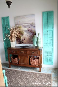 A pretty coastal entry way....Old Shutters painted a bold aqua color flanking a beach scene and entry piece....very welcoming..