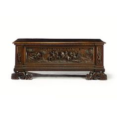 A NORTH ITALIAN WALNUT CASSONE 18TH CENTURY the hinged top with dentil frieze above a front inset with a panel boldly carved with two opponents on horseback slaying eachother, a fortified castle in the background, raised on grotesque carved feet height 65cm., width 160cm., depth 51cm.