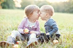 baby and his sister touch noses and kiss in a sibling portrait