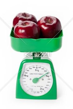 red apples weighed - Three red apples weighed on a green scale.